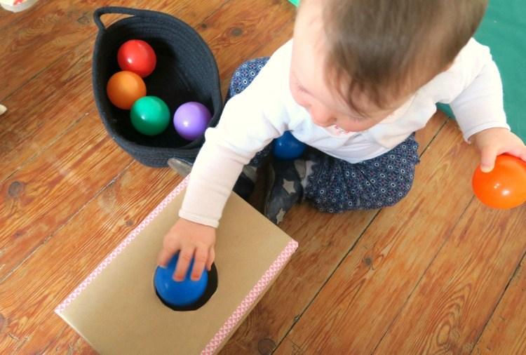 bébé-joue-avec-balle-dans-boite-permanence-objet.jpg