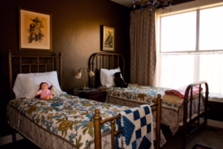 Located in Park City, Utah where bluebird skies are the norm. The antique brass and iron beds which the owner's children slept in when they were little was the design starting point.The walls were painted a semi-gloss antique dark brassy color and the trim painted a creamy white  to carry the masculinity of the beds. Crewel bedspreads, antique quilts and lots of artwork both modern and with age accessorize  this room, adding interest and freshness.