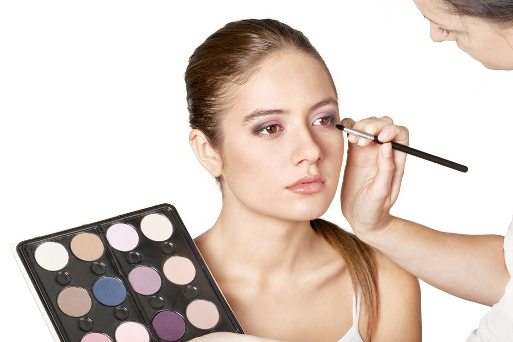 A makeup artist applies eyeshadow to a woman