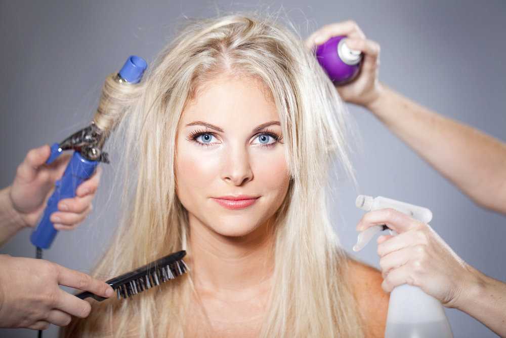 A woman being groomed with several different products and tools at once