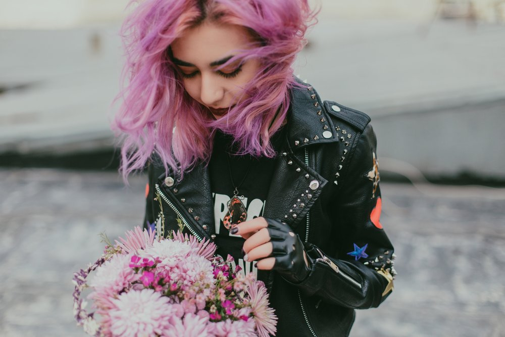 A girl with pink hair holds a bouquet of flowers