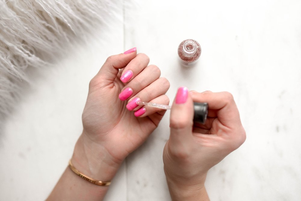 A woman painting her nails pink