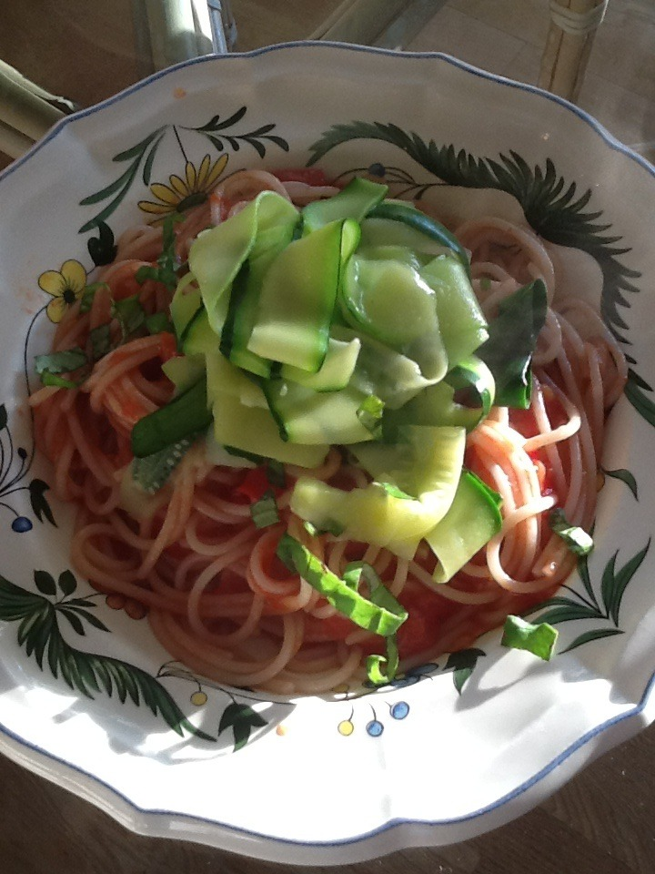 When my kids were little I would mix vegegetables into red pasta sauce to hide them. Now I can just put them on top. The early girl tomatoes are in the farmers market right now and they will not be around too much longer.  I just love the punch in their flavor. I made this pasta and got a little creative with the garnish of zucchini. It's a fun presentation and the zucchini folds into the pasta.   1 tsp. sea  salt  1 box spelt or your favorite pasta  2 Tbsp. olive oil  10-12 early girl tomatoes  1-2 cloves minced garlic  1 medium size zucchini   2 Tbsp fresh basil    Being a pot of salted water to a boil for the pasta    For the sauce  Heat a saucepan with 2 tablespoons of olive oil.  Cut up 12 early girl red tomatoes, add to the pan.   Mince 1-2 cloves of garlic. Add right on top of the tomatoes.  Cook for 10 minutes, using a fork, occasionally smash the tomatoes. If the sauce is too thick, add a spoonful of the pasta water.     Using a vegetable peeler, peel the zucchini unto long strips.    Drop Into the boiling water for 1 minute.  Remove from the pan, cover and set aside. Add the pasta to the water and cook according to package directions.      When the pasta is done, drain, and put in the pan with the sauce.  Add the basil and stir.  Place the pasta into individual bowls and put a portion of the zucchini on top.