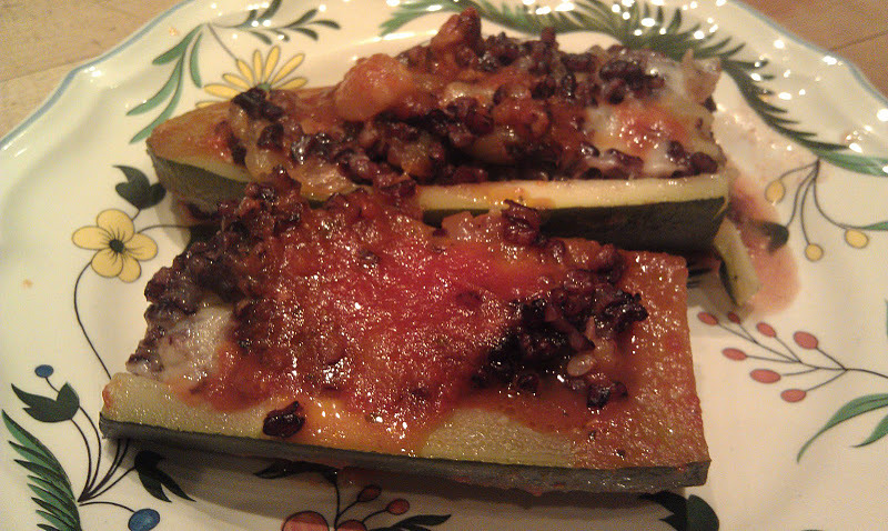 "Stuffed Zucchini    We ate this over two nights and it was so yummy. The squash is so good right now at the farmers markets and I found two large zucchinis to stuff. You can use any size, the larger ones work better.    2 Medium to  Large Zucchini    1 cup Japonica rice   2 ½ cups water   ¼ tsp sea salt    1 onion, sliced thinly   1 clove garlic finely minced   2 Tbsp. Olive oil   3 ounces fresh mozzarella cheese, diced (optional)   1 cup marinara sauce    salt and pepper   Bring salted water to a boil. Add the rice and cook for 45 minutes. (You can  also cook the rice in a rice cooker) In a large skillet, heat the olive oil and add the onion, cook for 10 minutes. Add the garlic. Using a melon ball spoon, scoop out the flesh of the zucchini. You will be left with a pile of zucchini balls and 4 clean zucchini ""boats"" ready for filling. Cut the zucchini balls in ¼'s and add to the onions. Season with a little more salt and pepper to taste. When the rice is done, add 1 cup to the onions and zucchini mixture. Mix together and correct your seasoning. stir in ½ of the cheese and reserve the other half.  To assemble. Pour the tomato marinara on to the bottom of a baking dish. Place the zucchini boats into the casserole. Fill each piece with the rice onion mixture. Top with the remaining cheese. Cover with tin foil and  bake in a preheated 350 degree oven for 45 minutes -1 hour.    Below you will see the before and after pictures of this dish. I hope you like it."