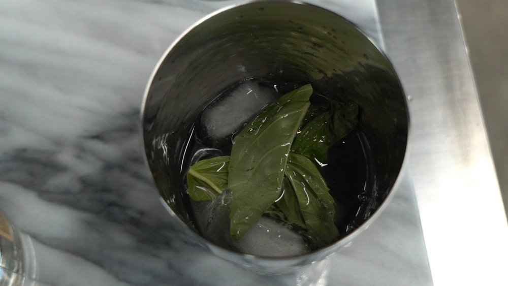 basil leaves, vodka, and ice after shaking