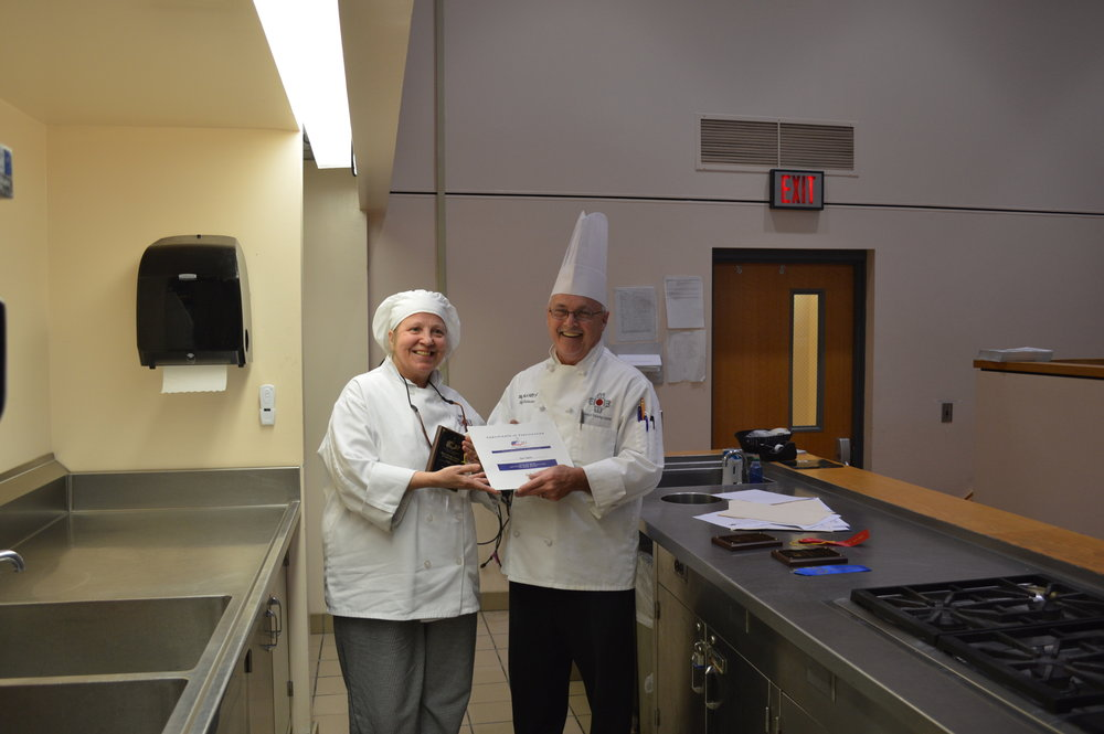 Chef Chuck Baux presents Corrinne Wessel with 3rd place for her Hungarian Chicken Salad