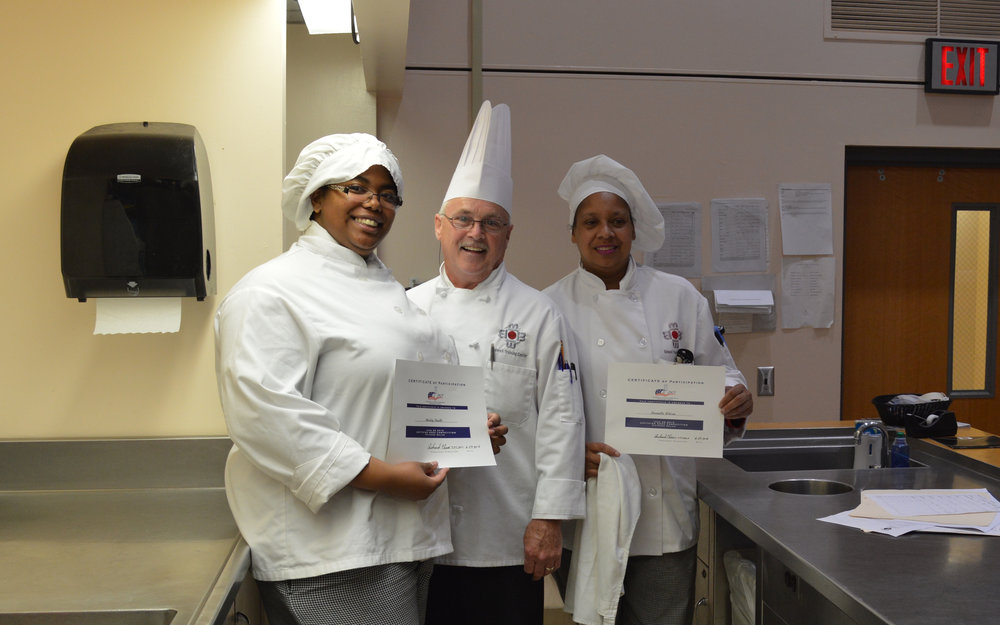 Darnella Wilson (Spicy Chicken Melee) and Marley Fawlks (Bombay Chicken Salad) accept participation certificates from Chef Chuck Baux