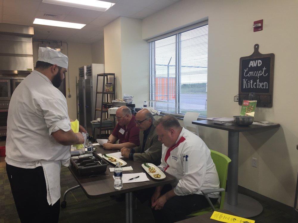 Raymon Mender Presenting his plate to judges Scott Burkhart, Bill Hunt, and John Selick.jpg