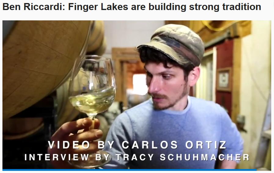 Benjamin Riccardi holding a glass of chardonnay alongside barrels
