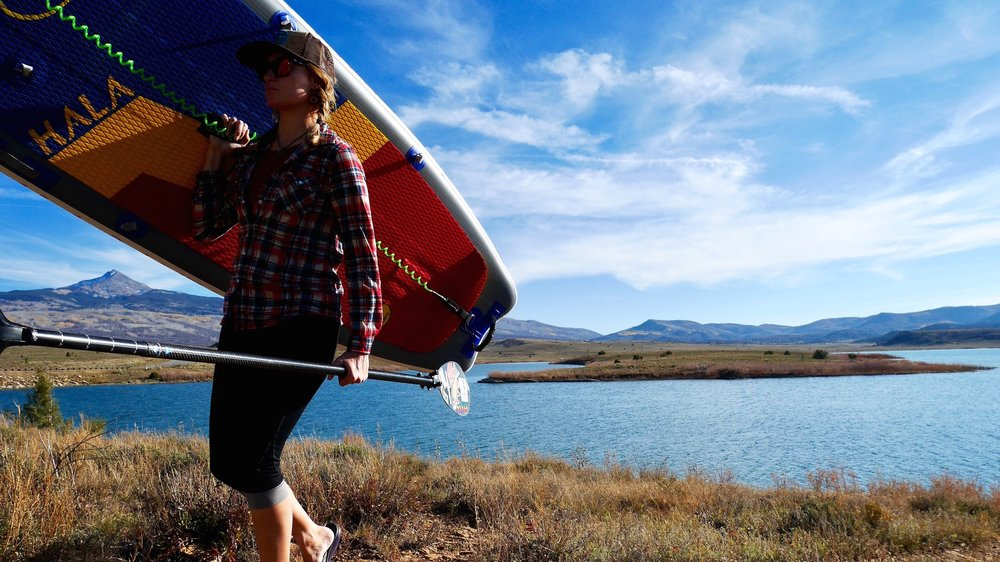 Carrying stand up paddle board at Miramonte Reservoir near Norwood Colorado