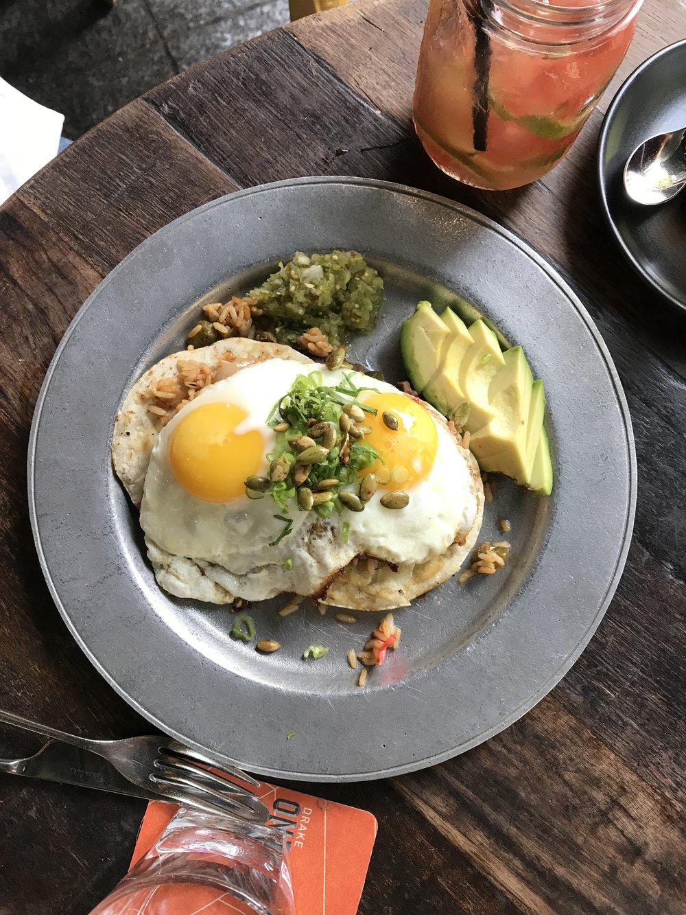 Huevos Rancheros - Refried black beans, sunny side up eggs, chili spiced rice,avocado, tomatillo salsa