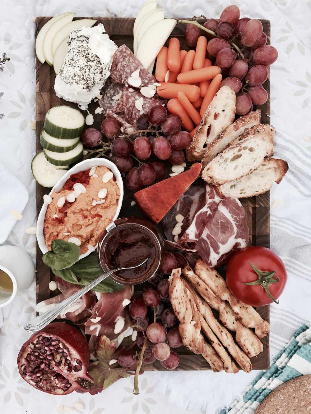 We included: - - Roasted red pepper hummus- Cucumber- Carrots- Proscuitto- Genoa salami- Coppa di parma- Red grapes- Smoked cheddar- Herbed goats cheese- Toasted baguette- Cracker sticks- Greek tomato paste