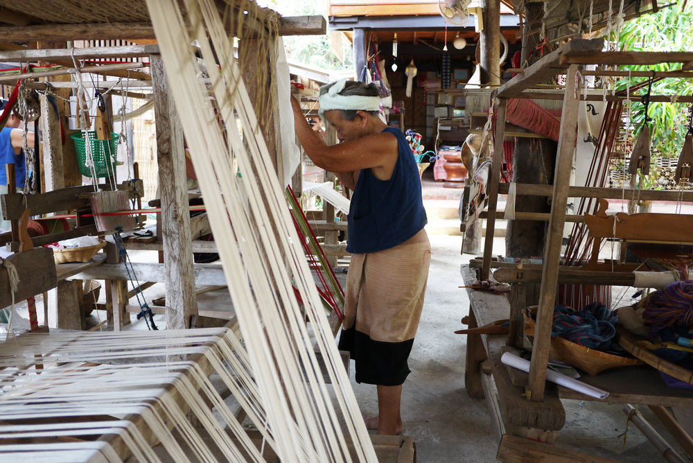 A weaver setting up her loom in Mae Chaem