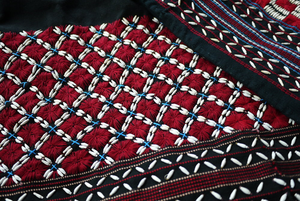 Detail of an embroidered tunic that uses the Karen's signature palette of black, red and white.