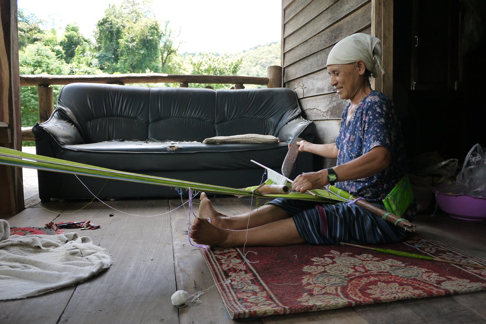 A weaver working on her house balcony, with a backstrap loom in Mae Takri, Doi Saket District, Chiang Mai Province.