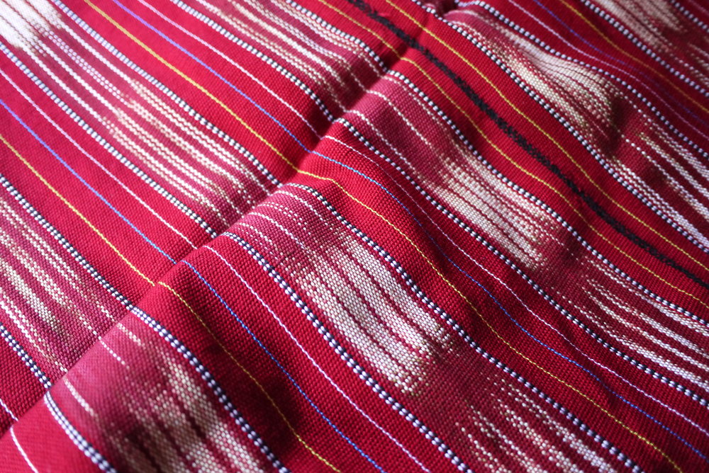 Detail of a red tube skirt which is typically worn by the Karen women.