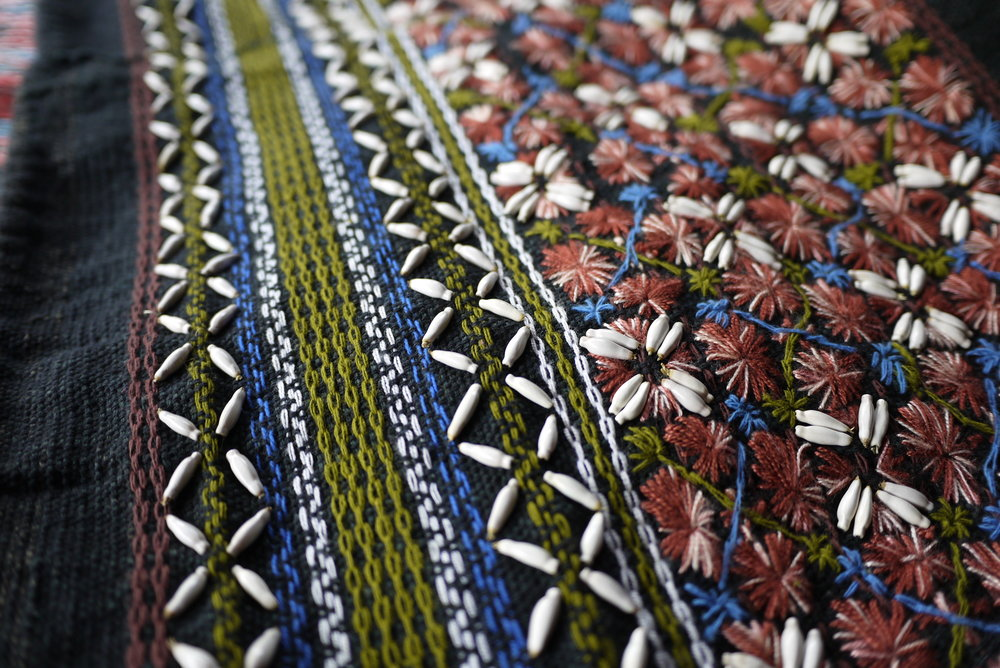 Detail of an embroidered tunic using local fruit seeds as ornaments. This community in Doi Saket has re-introduced the use of natural dyes in recent years through the support of a training programme.