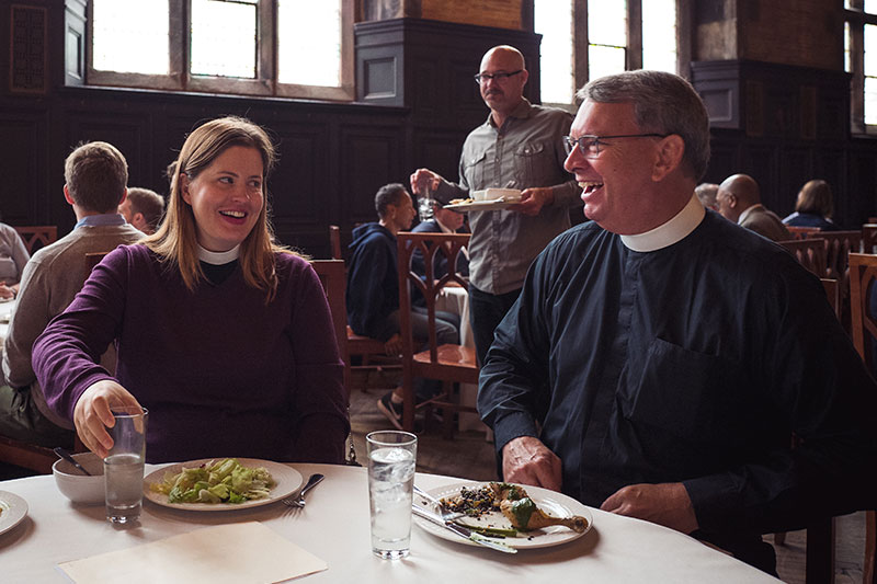 Faculty sharing a laugh during a meal at The General Theological Seminary