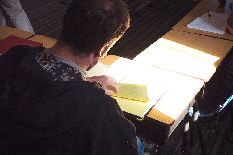 A student is taking notes during class at General Seminary