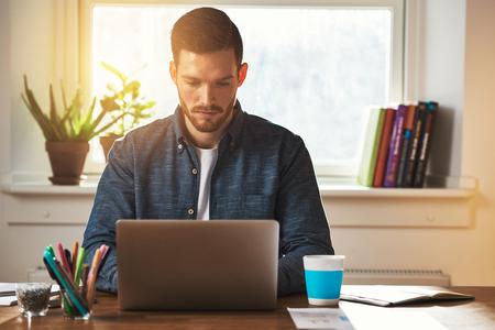 54384131_S_man_working_computer_laptop_browsing_internet_studying.jpg