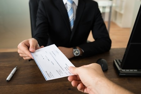 44315690_S_wages_pay_check_corporate_business_man_woman_hands_receiving_money_office_desk.jpg