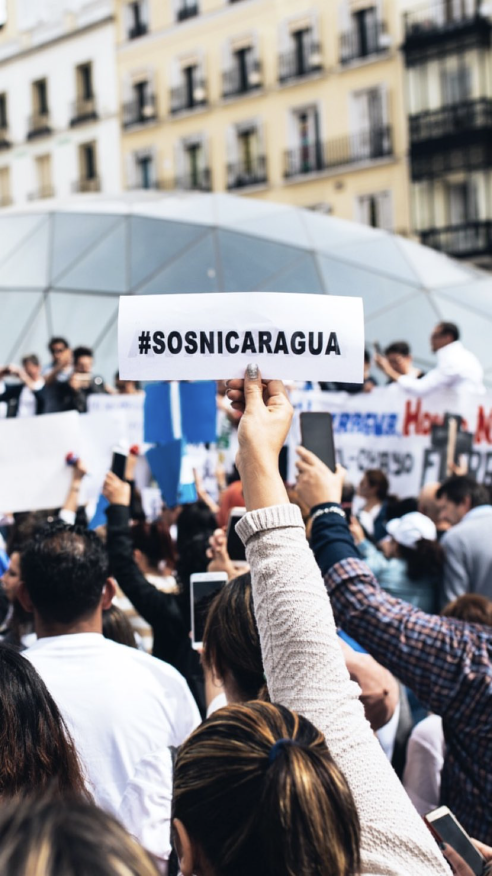 "Photo of a young woman during a protest in Spain holding a sign that reads ""#SOSNICARAGUA""--the hashtag campaign being used by the Nicaraguan community to spread awareness on the events taking place, for the Nicaraguan people to follow the crisis, and to organize in Nicaragua. The Nicaraguan community outside Nicaragua are also utilizing the hashtag to show solidarity and support. (Photo by   David Salazar )"