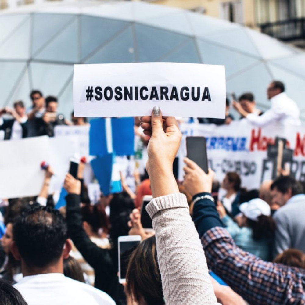 """Photo of a young woman during a protest in Spain holding a sign that reads """"#SOSNICARAGUA""""--the hashtag campaign being used by the Nicaraguan community to spread awareness on the events taking place, for the Nicaraguan people to follow the crisis, and to organize in Nicaragua. The Nicaraguan community outside Nicaragua are also utilizing the hashtag to show solidarity and support. (Photo by   David Salazar )"""