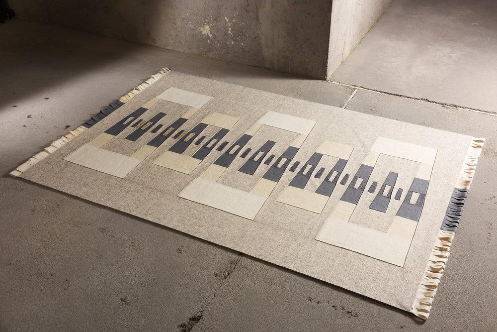"""PIÉ Szőnyeg - Célközönség: Design iránt fogékony emberekFunkció: Gyapjú szőnyegGyártó: Saját kivitelezésMéret: 135 cm x 245 cmTechnika: Egyedi fűzésAnyaghasználat: 3 mm-es gyapjúfilc, 2 mm-es újrahasznosított filc végszélTermékismertetőA """"PIÉ"""" lakástextil kollekcióhoz tervezett, gyapjú szőnyeg. Alapja 5 mm vastag """"melange"""" gyapjúfilc, melyre kézi, fűzött technikával kerülnek rétegek, ezzel alakítva ki azt a finom optikai hatást, mely a kollekció többi – lapfüggöny, lámpa – tagjával közös. Geometriája a """"PIÉ"""" kollekcióba illeszkedik, de a függönyök varrott piéinek"""