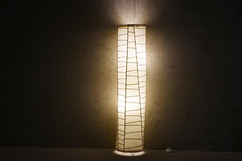 """PIÉ Lámpa család - Célközönség: UniverzálisFunkció: VilágításGyártó: Saját kivitelezésMéret: d: 50 cm x 110 cm állólámpa, d: 60 cm x 140 cm függeszték lámpaTechnika: Egyedi pié varrásAnyaghasználat: GyapjúfilcTermékismertetőA """"PIÉ"""" lakástextil kollekcióhoz tervezett, lámpacsalád. Anyaga 0,5 mm vastag, nyers, gyapjúfilc, mely belülről megvilágítva a filc lágy struktúráját mutatja meg a """"pié"""" varrások vonalas rendje között. Ezzel a puha-felhőszerű ugyanakkor éles-vonalas kontraszttal illeszkedik a kollekció többi – lapfüggöny, szőnyeg - tagjához."""