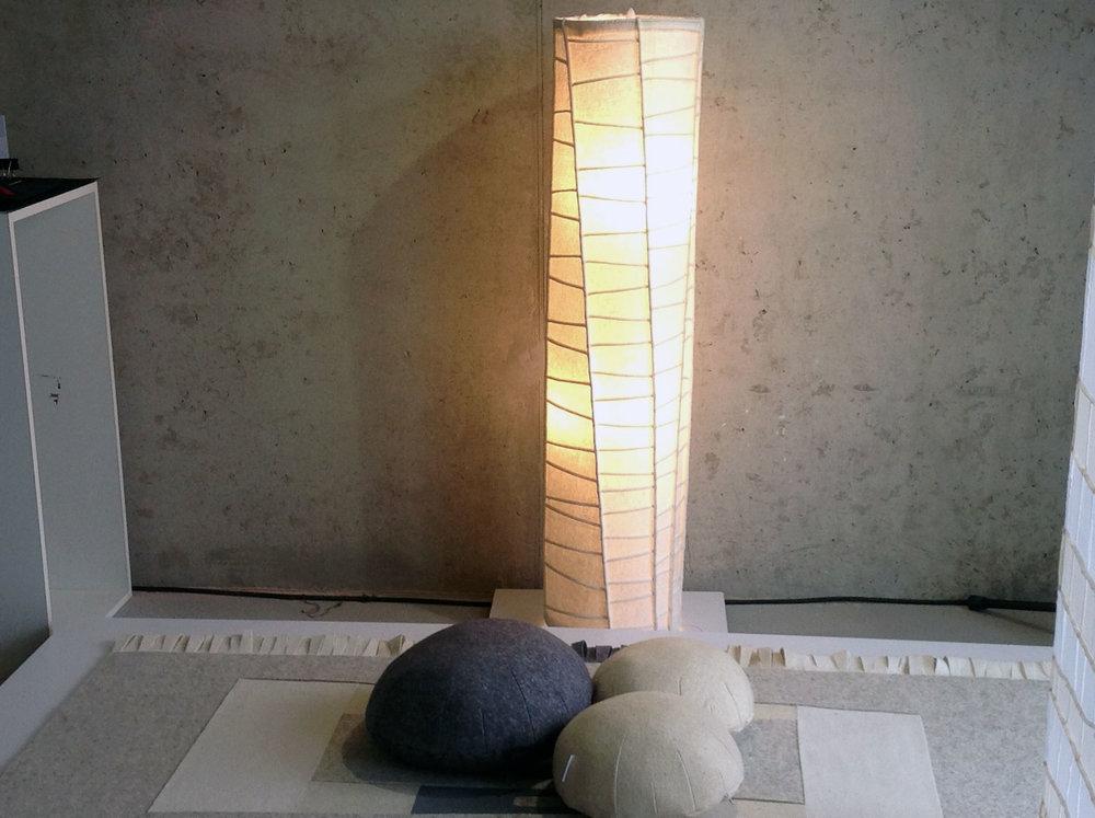 """pié lámpa - Tervező: Ambrus ÁgnesGyártó: Saját kivitelezésMéret: d: 50 cm x 110 cm állólámpa, d: 60 cm x 140 cm függeszték lámpaTechnika: Egyedi pié varrásAnyaghasználat: GyapjúfilcA """"PIÉ"""" lakástextil kollekcióhoz tervezett, lámpacsalád anyaga 0,5 mm vastag, nyers, gyapjúfilc, mely belülről megvilágítva a filc lágy struktúráját mutatja meg a """"pié"""" varrások vonalas rendje között. Ezzel a puha-felhőszerű ugyanakkor éles-vonalas kontraszttal illeszkedik a kollekció többi – lapfüggöny, szőnyeg - eleméhez."""