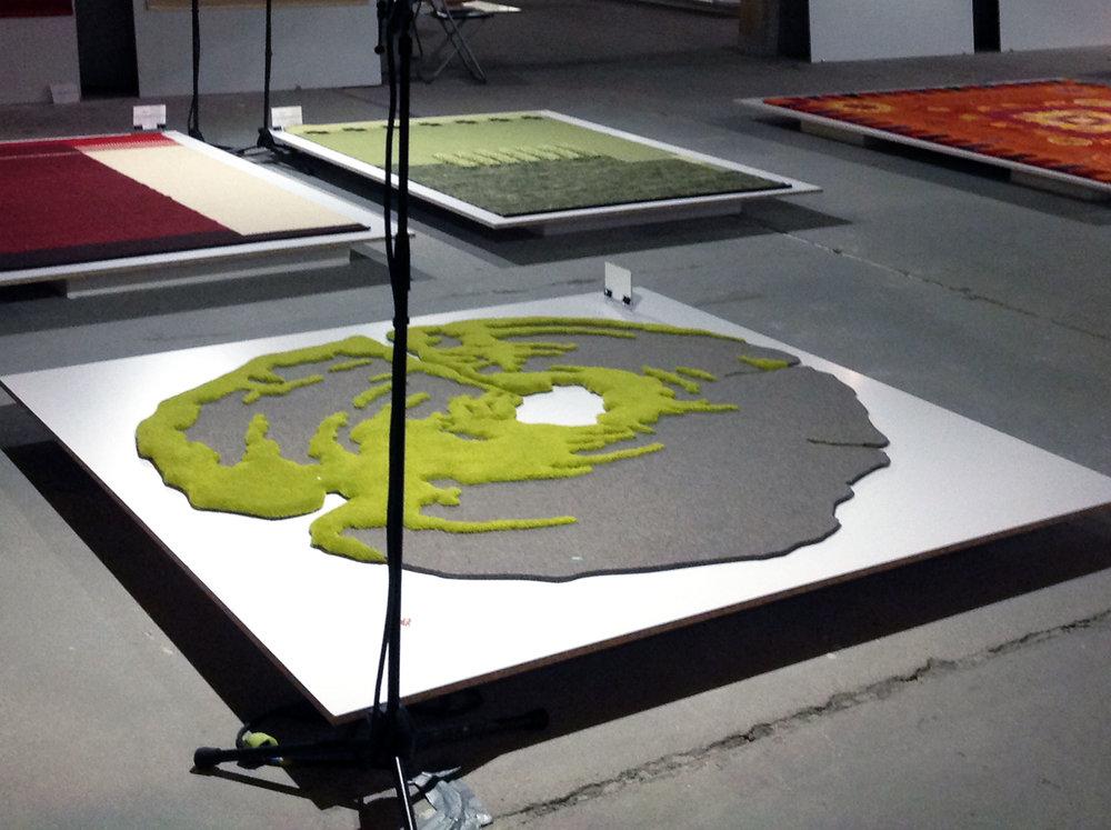 FELT AND TUFTED termékcsalád-WOOD - Tervező: Brinkus-Vándor KataGyártó: MB Rug Kft., Unimark, Brinkus DesignMéret: 180 cm átmérőTechnika: ApplikációAnyaghasználat: gyapjú ipari filc, gyapjú fonalTermékismertető:A Felt and Tufted termékcsalád tervezésének motivációja, olyan nem szövéssel előállított szőnyeg felület létrehozása, mely alkalmas nagyobb igénybevételnek kitett terekben, étkezőkben, tárgyalókban, folyosókon, stb. is helytállni. Az ipari filc sűrűsége, felülete tökéletesen megfelel belső terek meleg burkolataként. A két matériával, filc és tűzött felület gazdag plasztikai és grafikai megjelenés érhető el.