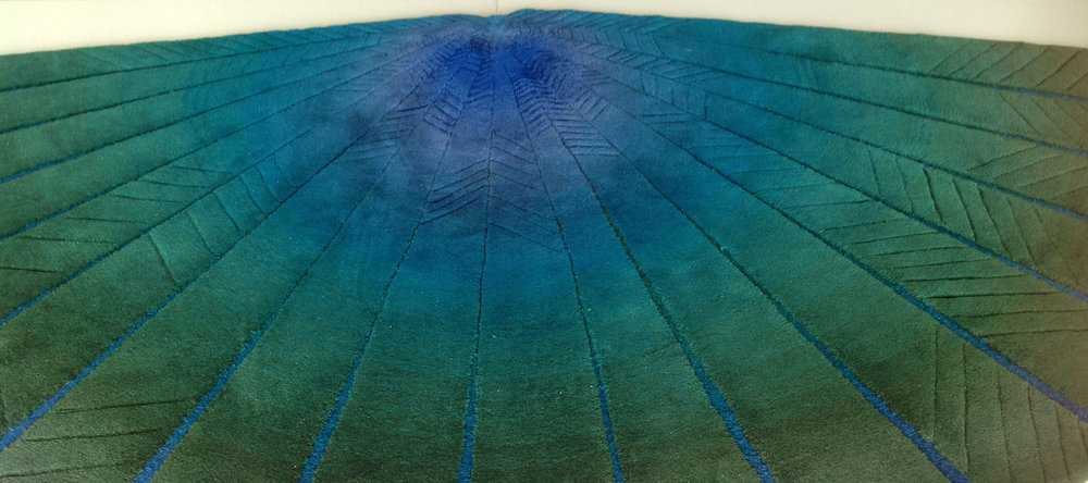 BLUE FAN – KÉK LEGYEZŐ - Tervező: Gulyás JuditTermékismertető: Egyedi tervezésű kortárs design szőnyeg, 100 % gyapjúból készült, hand-tufting (kézi tűzés) technikával.A legyező – különböző szögben nyitott körcikkek – formai játékával lágyítja a teret, a bútorozásban túltengő kubusok mellett finom ívet rajzol elegáns, nagyvonalú megjelenésével. Színátmenete a pávatollak árnyalatait is idézi (szárny-legyező szimbólum), a középpontba futó szeletek mélyebb részén, a buklé technikával szőtt árkokban megfordul a színátmenet. Ez az apró játék még inkább kiemeli a lamellákat. Formai játéka mellett elsődlegesen mégis szőnyeg, padlóra és falra egyaránt kerülhet.