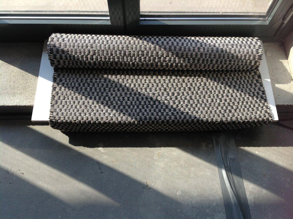 RUSTICUS és URBANIST - Tervező: Szentiványi-Székely EnikőGyártó: Saját kivitelezésMéret: 100 cm x 165 cmTechnika: Kézi szövésAnyaghasználat: Sodrott papírfonal, pamutTermékismertető: Az Intermezzó és Okapi a sötét világos kontrasztjára épül. A homogenitás egyszerre benne van a nagy fehér felületben illetve a fekete és fehér fonalak váltakozásában. Ezáltal bármilyen enteriőrben használhatók, nem uralják a teret. A Rusticus és Urbanus a megművelt föld és a modern építészet grafikáit adja vissza. Minimál és klasszikus belső terekben egyaránt jól mutatnak geometrikus mintázatukkal.