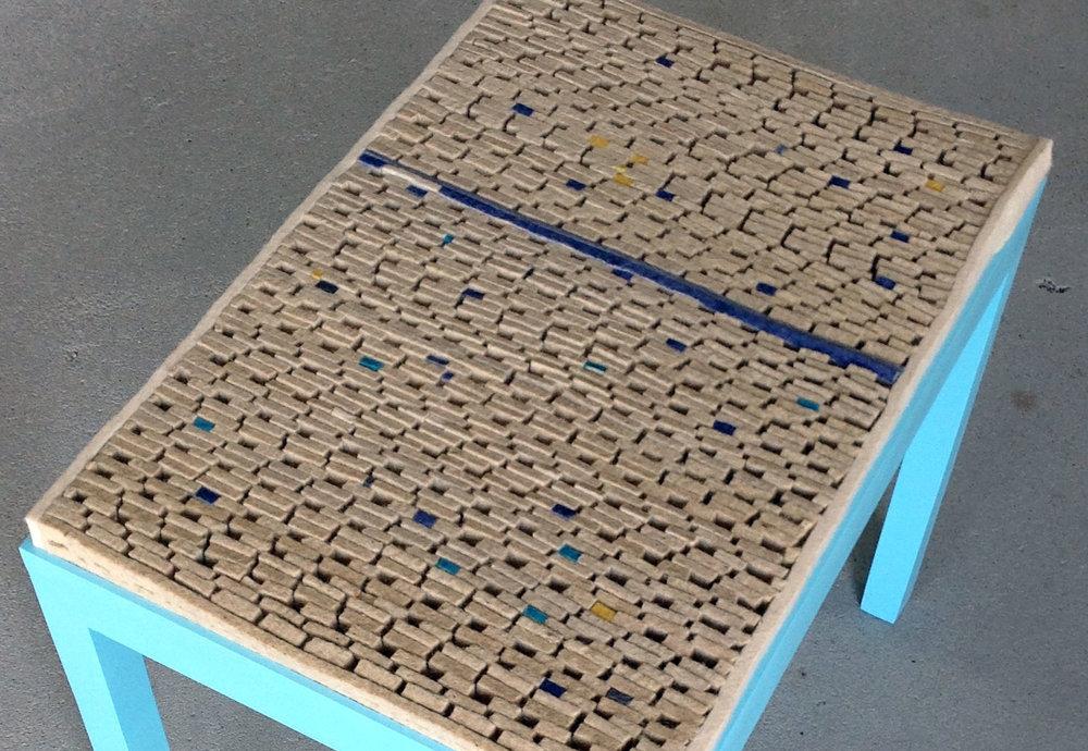 STOKI ülőbútorok - Terveök: Temesi Apolka és Bucsi ÁrpádGyártó: Saját kivitelezésMéret: 50 cm x 30 cm x 40 cmTechnika: egyéni technikaAnyaghasználat: ipari filc hulladékTermékismertető: A STOKI bútor család karakterét a bújtatott, préselt ipari filc határozza meg. Az ülő bútorok nemcsak az ipari filc újszerű felületalakítási lehetőségeit mutatják be, de ezzel együtt alakítani is kívánják az ipari hulladékról alkotott elképzeléseinket. A bútor család minden darabja ipari filc hulladék újraértelmezésének igényéből született, ahol az anyag megmunkálásával annak új karaktere bontakozik ki