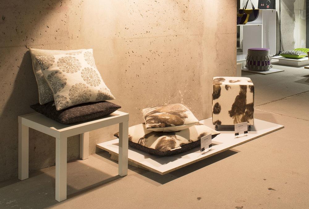MAGYAR TARKA – fekvőpárna és puff - Gyártó: LakbearMéret: 70 cm x 70 cm, 40 x 40 cmTechnika: Kézi applikációAnyaghasználat: Gyapjúfilc, természetes színezékekkel festett gyapjúTermékismertető: A fekvőpárna alapanyaga a MultiFelt Factory gyárában készült, 100% ausztrál merinói gyapjúból. A fehér alapra különféle természetes és növényi színezékekkel megfestett gyapjúszálak kerültek, így adva a foltosan mintás filcet. A fekvőpárna (padlóra helyezhető) különlegességét a filcanyag gyári és kézi megmunkálással történt készítése és a természetes anyagokkal, mint diópáccal és vöröshagymával megfestett gyapjúszálai adják.PuffMéret: 50 cm x 40 x 40 cmTermékismertetőEgyszerű ülőbútor kerekekkel, amely nem foglal nagy helyet, könnyen mozdítható. Lényegében egy szivacskocka, falapon melynek vannak kerekei. Ez az alap van bevonva gyapjúfilccel. A filcanyag megegyezik a 2. pontban leírt fekvőpárna anyagával. A gyártás során ugyanúgy készült a puff huzata, mint a padlóra helyezhető párnánál.