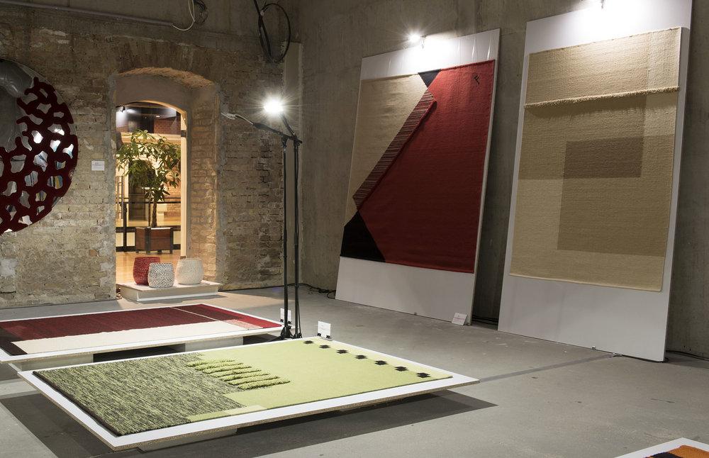 """Rétem szőnyegcsalád - Tervező: Füzesséry ErikaTermékismertető: Az épített és tárgyi környezetünk téri kompozíciójába szervesen társuló, és az apró, kézműves részletek örömét is adó szőnyegek tervezésére törekszem. Ebben a szellemben készültek a """"Rétem"""" (My Mead) kollekció kisszériás kézi szövésű szőnyegei a Csaba Szőnyeg Grafier Kft. kivitelező céggel együttműködve. A természet változatos, inspiráló mintázatai a szövési technikák szigorú törvényei mentén lényegülnek át szőnyeggé. A természetes alapanyag formai expresszivitását játékosan erősítik a szövött alapba csomózott, színes szálakból plasztikus részletek."""
