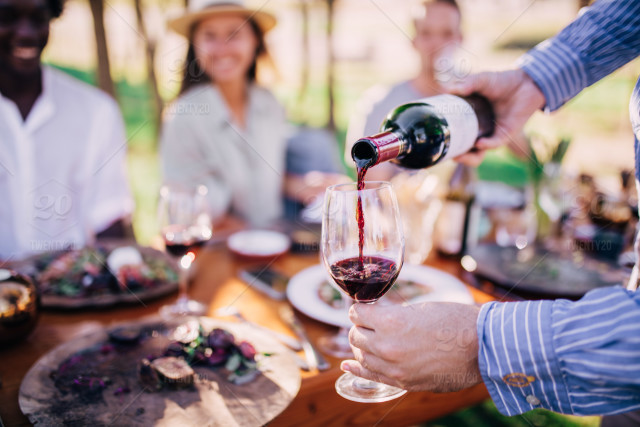 stock-photo-drink-alcohol-festive-lunch-eating-picnic-pouring-wine-together-1d4aa399-6000-42e9-b828-8efd44123bd8.jpg