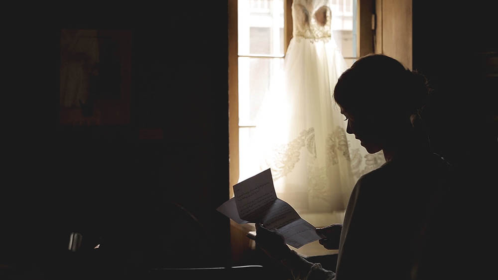 bride reading letter from groom on wedding day
