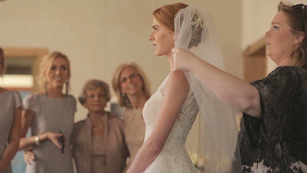 bride putting on veil as mother grandmother and sister watch