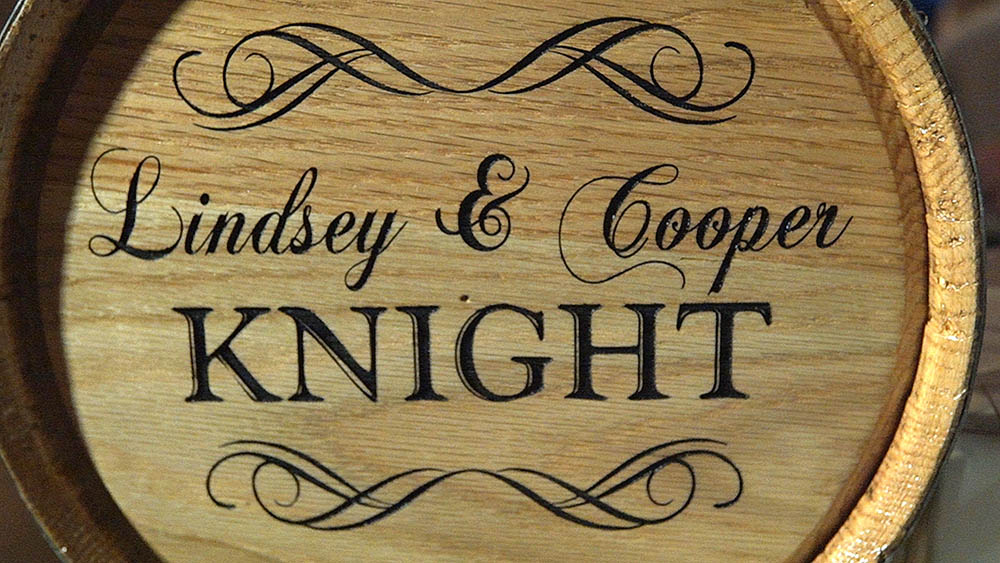 laser etched wine barrel at wedding with bride and groom name