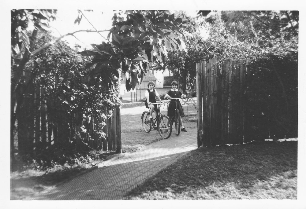 My sister Siri (left) with her friend, Penny Crosoer. The photo shows the wooden fence and brick walkway added to the side of the house for privacy. In the far back of the photo is the tennis court. Siri and Penny are wearing school uniforms.