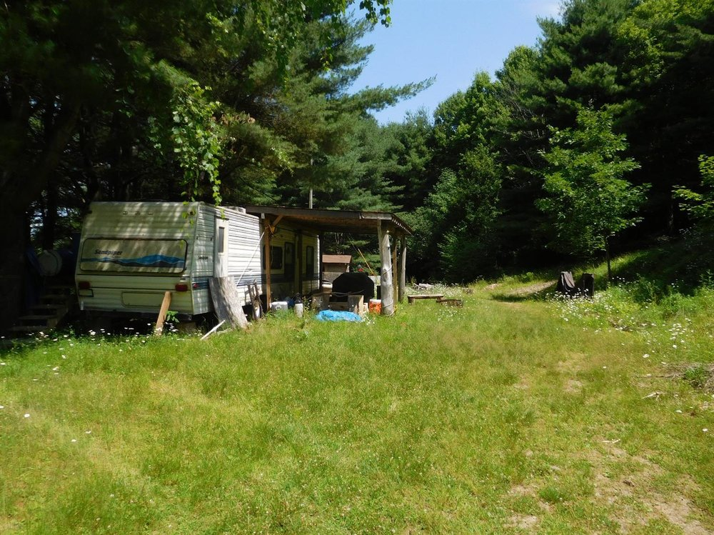 140,000 - 55 Acres, Mostly Wooded with Two Sheds, 35' Trailer and Electric