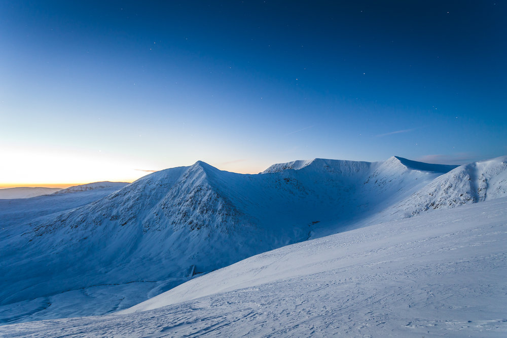 Helvellyn summit is visible in a fresh white cloak, as the last few stars cling to the sky