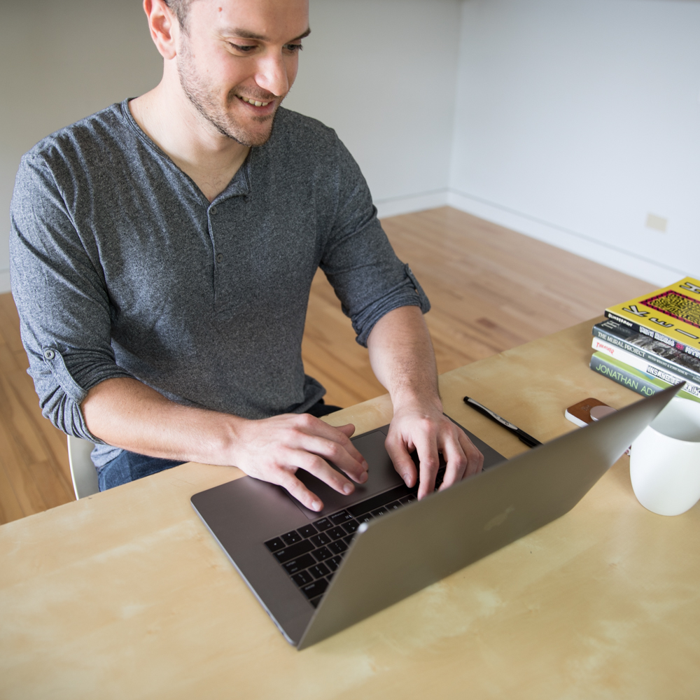 Person sitting at a laptop with coffee mug and stack of books nearby.