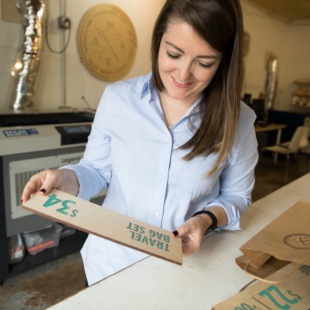 Woman holding the shop sign she just made at a laser cutting studio.