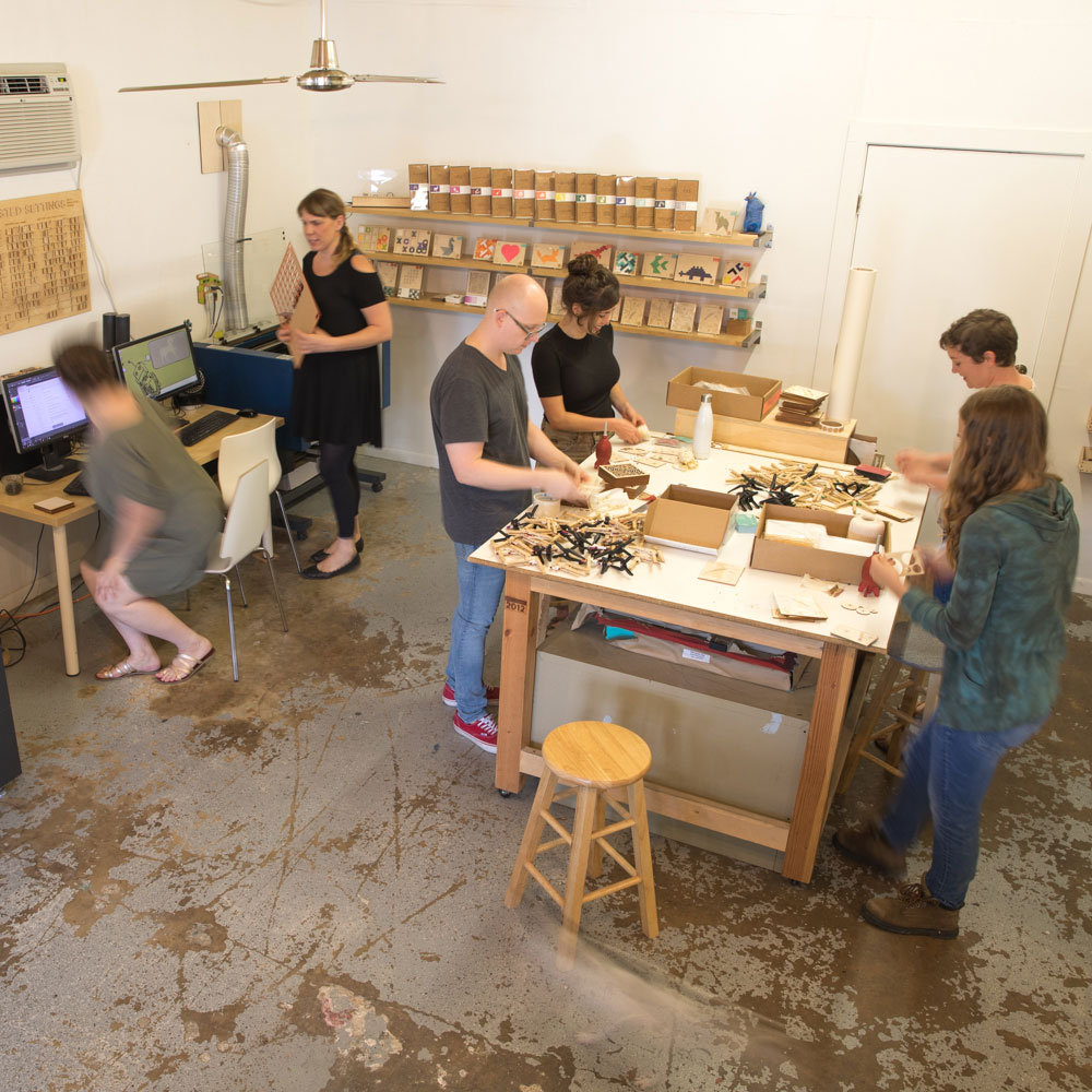 Laser cutting studio with artists creating new work.