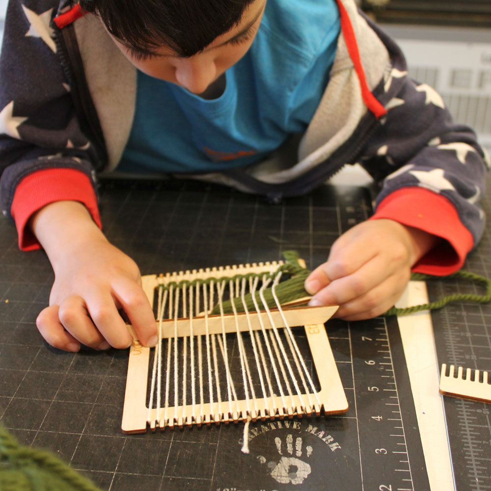 Child with a homemade loom at laser camp.