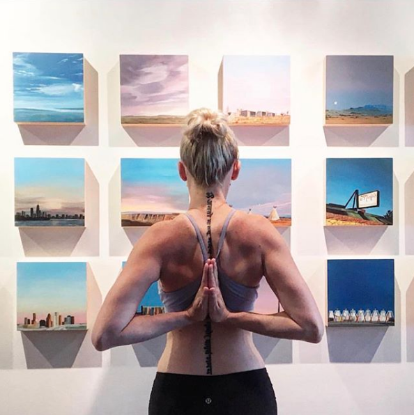 "@wanderlustinyogi posing in front of an installation of 8x8x2"" paintings at Aether Space Gallery in Houston. Photo courtesy of @blackswanyogahouston Instagram."