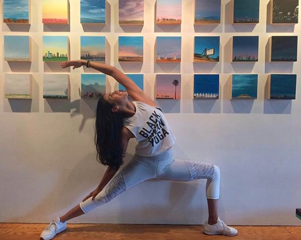 "@yogaandsuzy posing in front of an installation of 8x8x2"" paintings at Aether Space Gallery in Houston. Photo courtesy of @blackswanyogahouston Instagram."