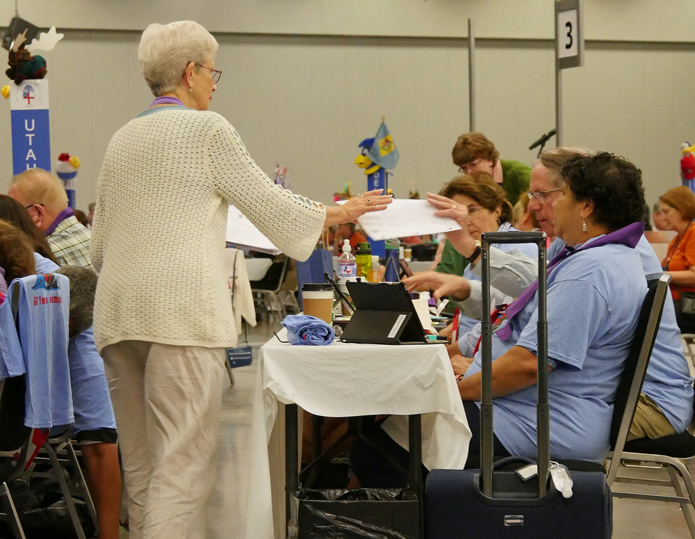 A volunteer collects diocesan votes on Resolution B012. Votes that are cast by orders (lay and ordained) are still done electronically but also have a paper record to accompany it. Photo credit to Episcopal News Service.